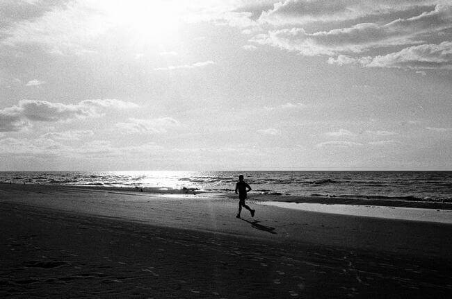 black-and-white-image-of-man-jogging-on-beach