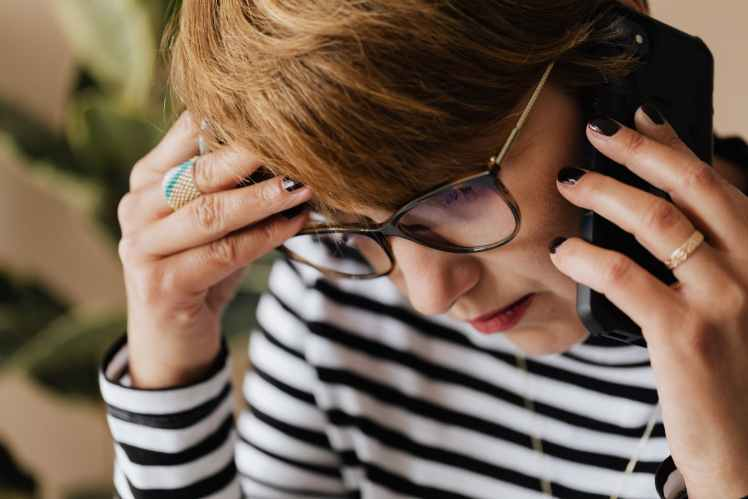 anxious woman having phone conversation in office