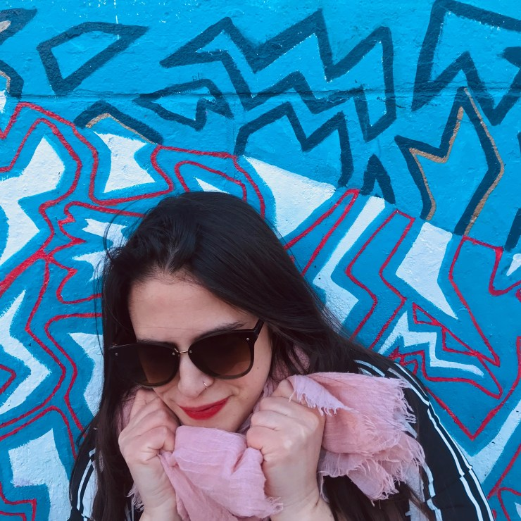 Brunette woman wearing sunglasses and a scarf giving herself of a squeeze in an act of self compassion