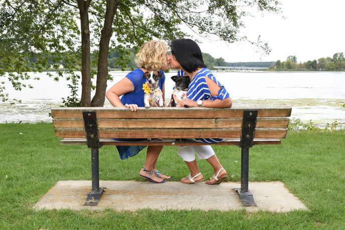 LGBT couple kissing on a park bench at wade's bayou memorial park