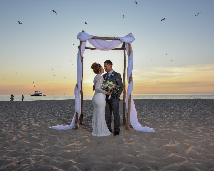couple under beach wedding abor