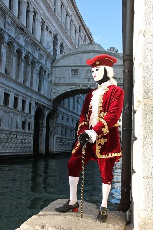 A gentleman stands in front of the famous Bridge of Sighs during Venice Carnival