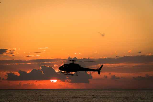 silhouette of airplane flying over the sea during sunset