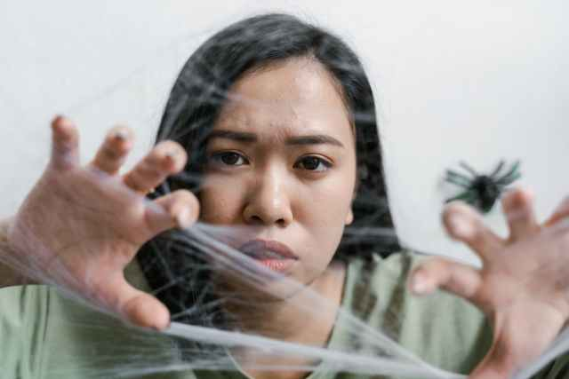 a helpless woman trapped in a spider web