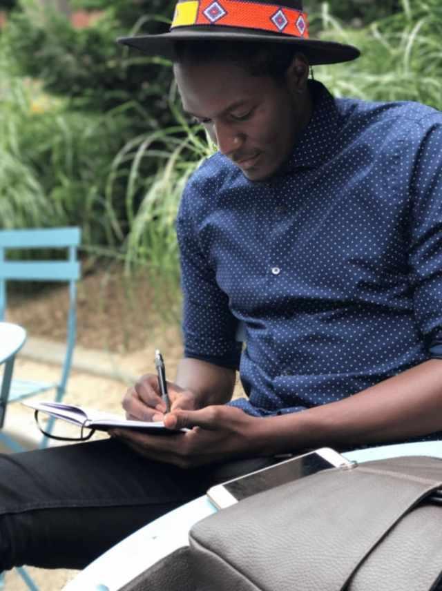 Dark Skin Man writting in journal