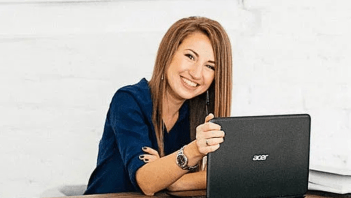 Lady at desk looking over her laptop