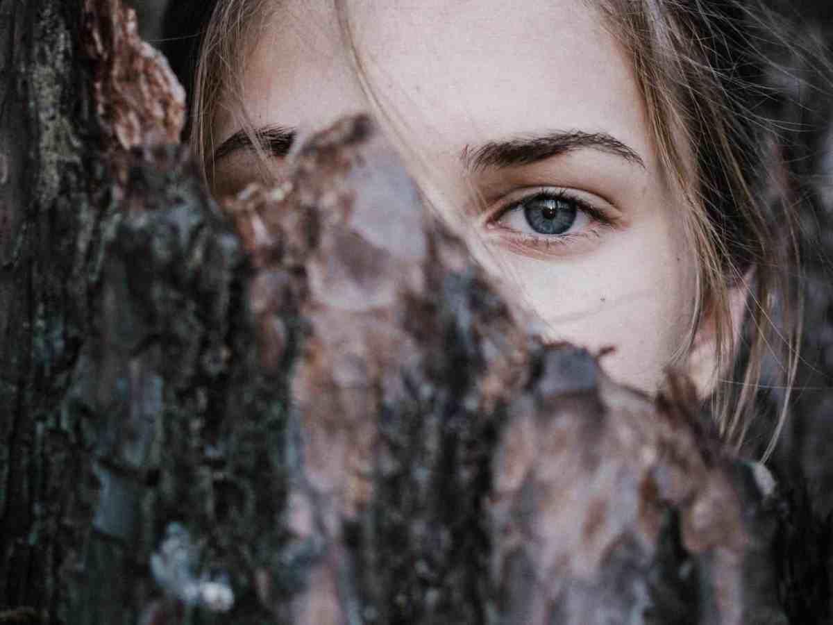 calm woman behind tree bark in park
