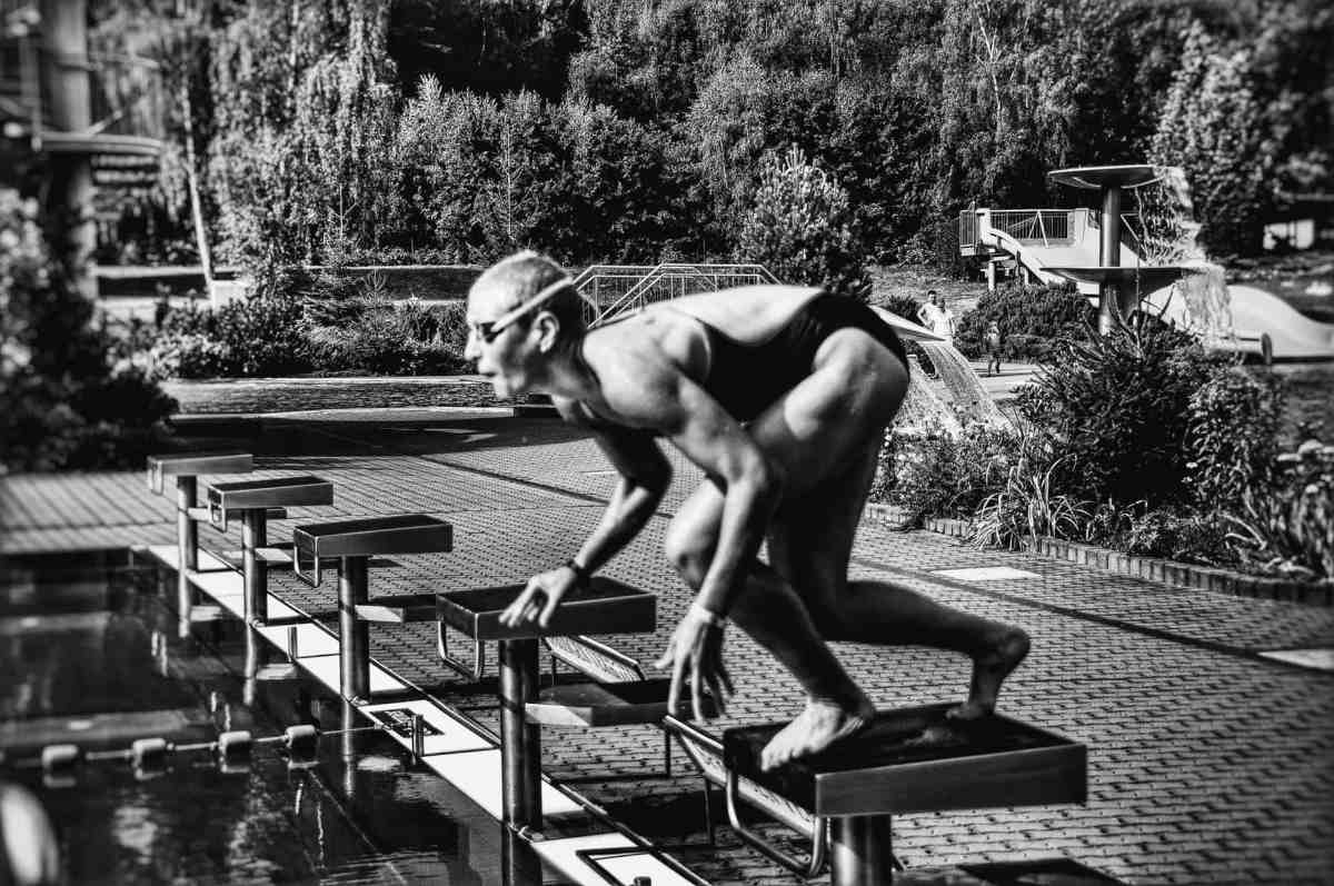 swimmer on block before diving into pool