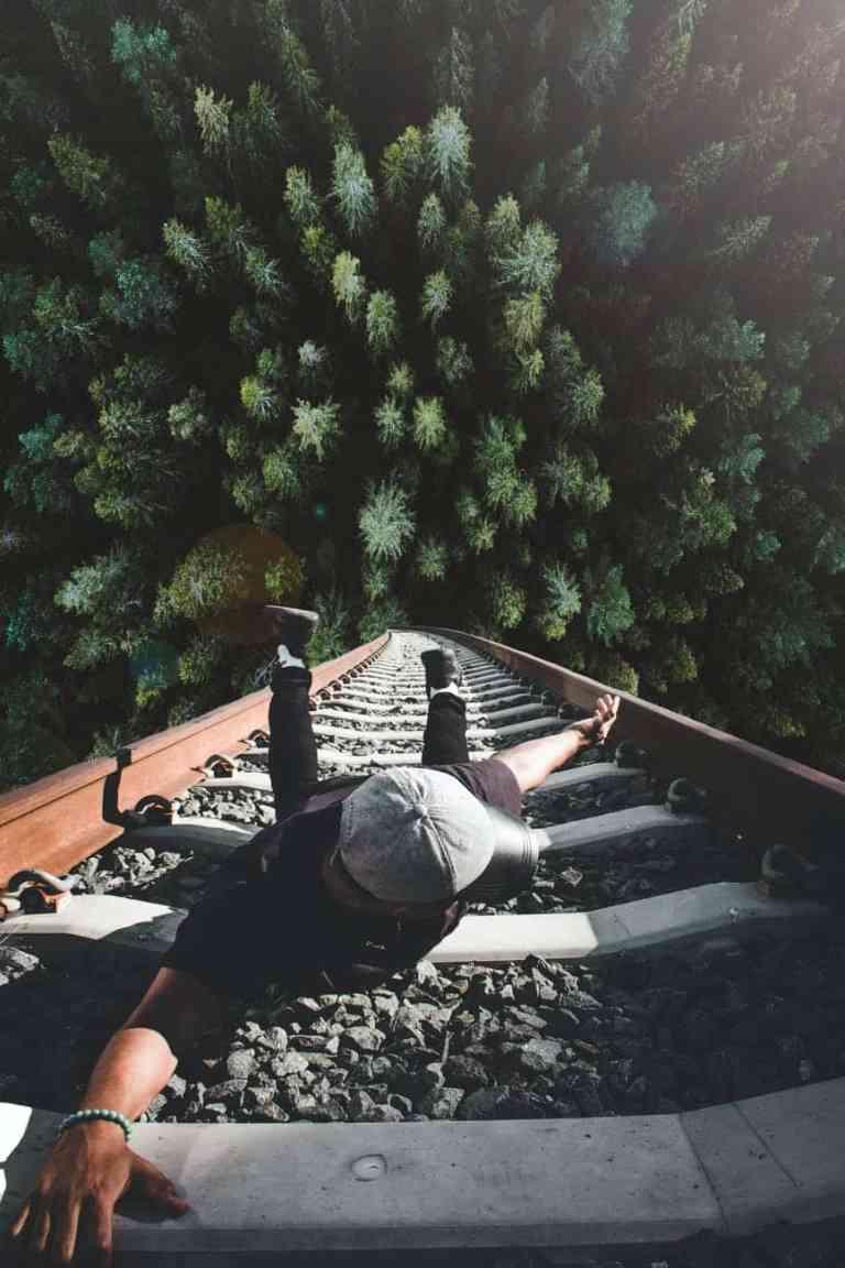 man holding on gray railing