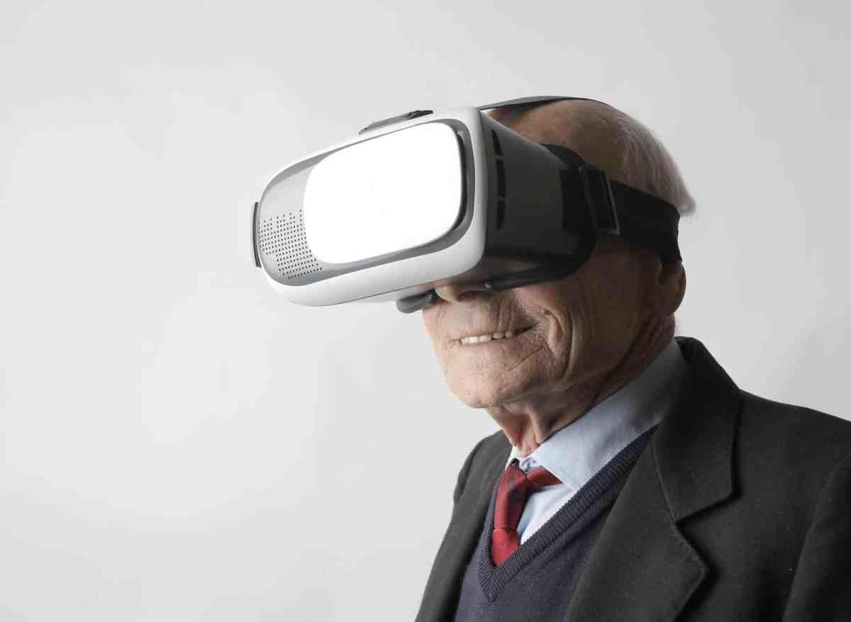 senior man using vr goggles in studio