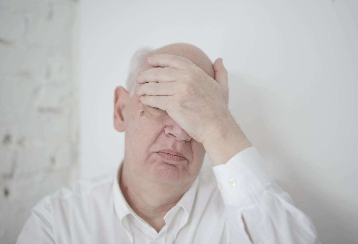 senior man covering face with hand while sitting near wall