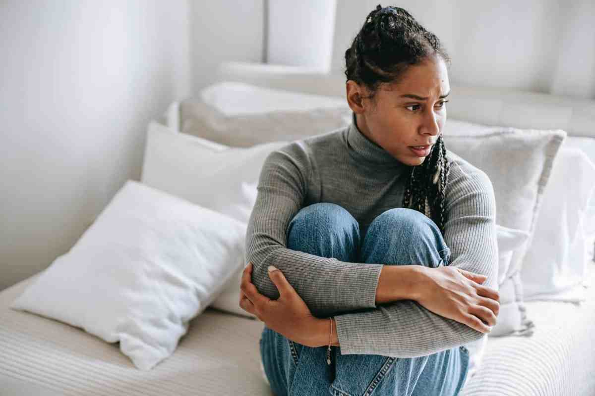 ethnic woman embracing knees and suffering from anxiety