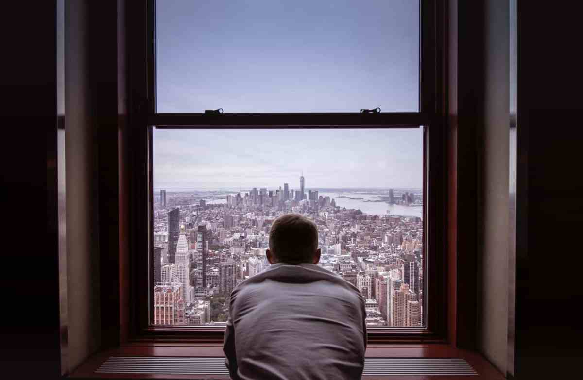 man in gray shirt looking at city buildings
