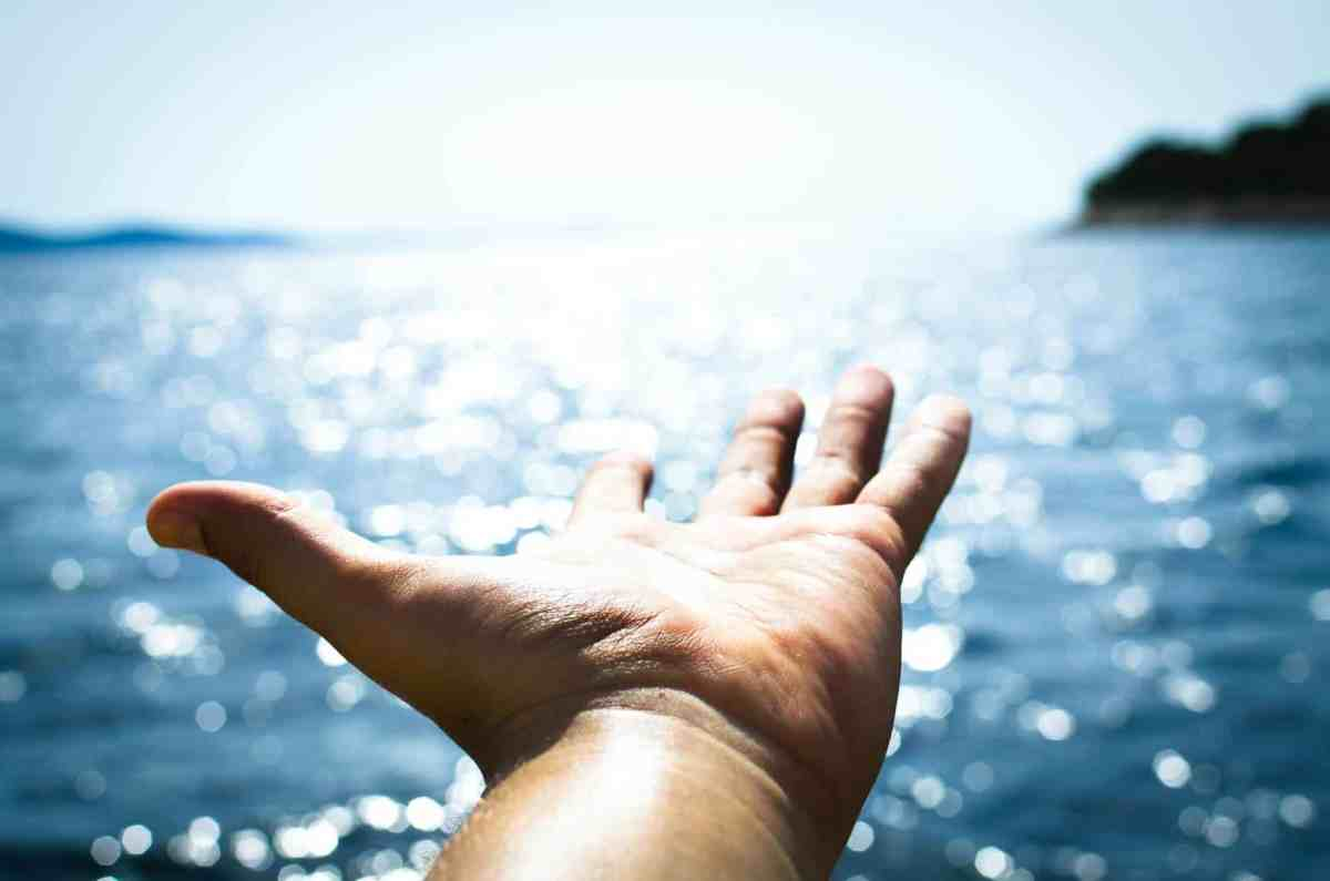 person hand reaching body of water - let hope be your guide