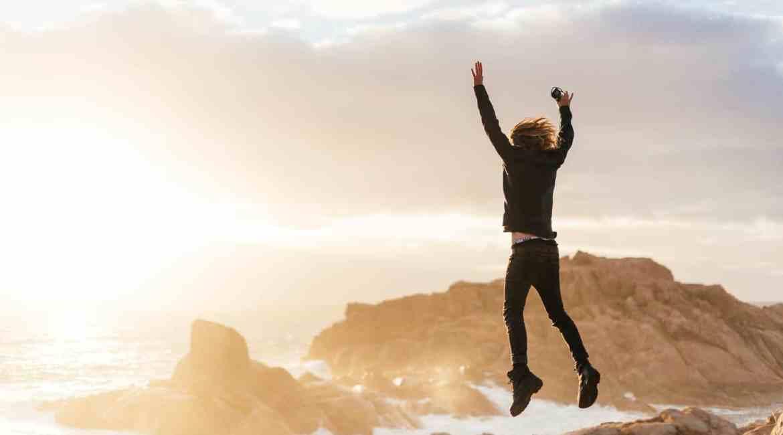 unrecognizable man jumping on stones near sea