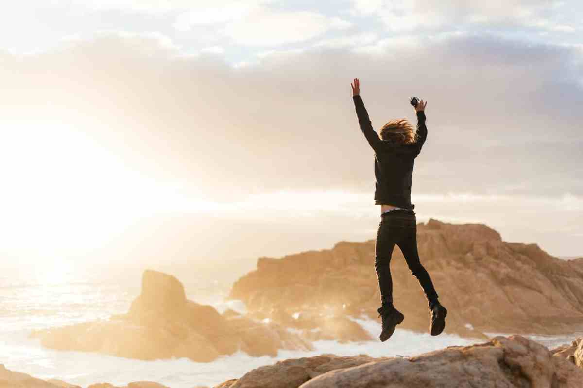 unrecognizable man jumping on stones near sea Showing up for yourself abundance