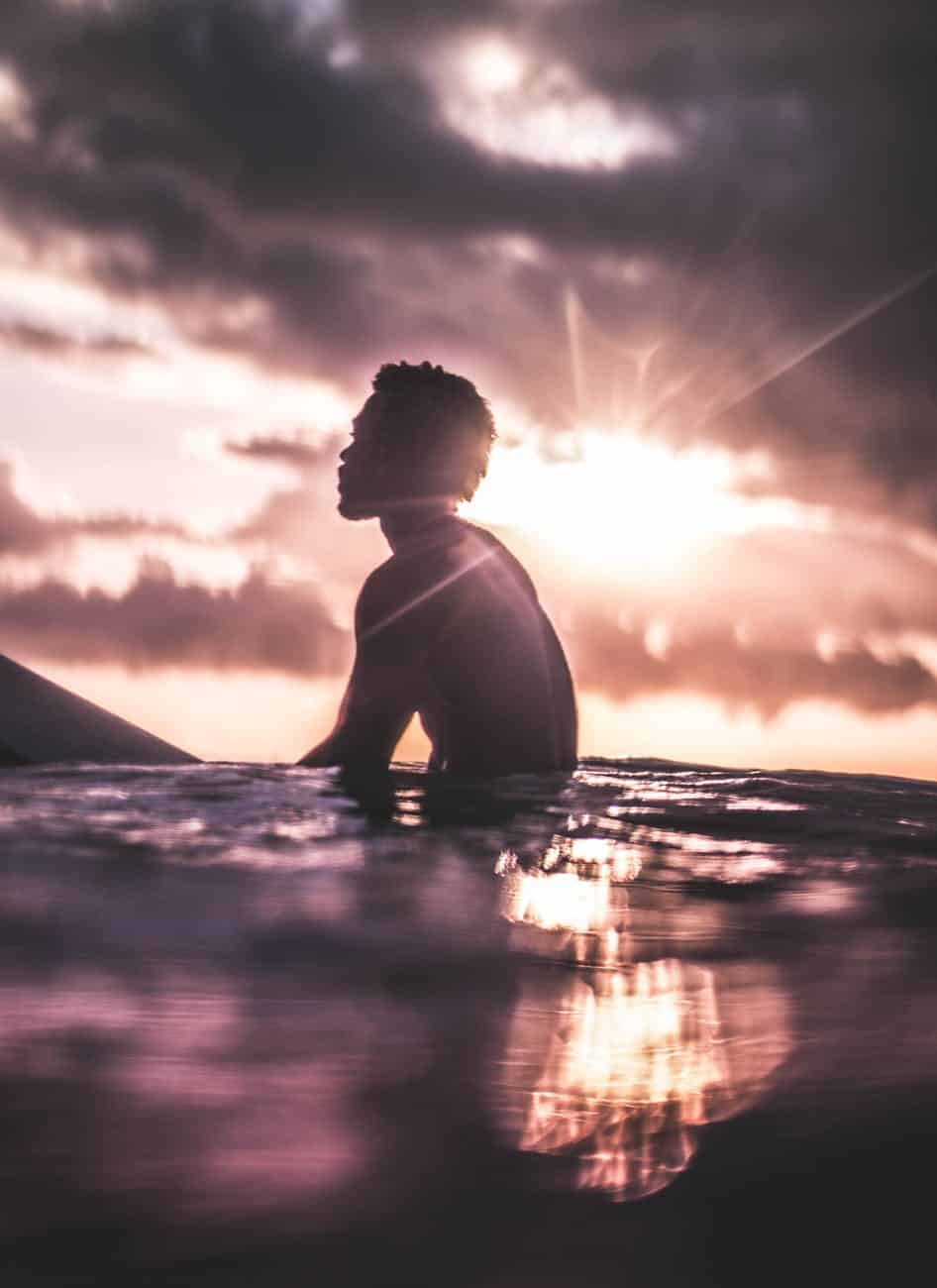 unrecognizable black man relaxing in sea water at sundown Showing up for yourself abundance