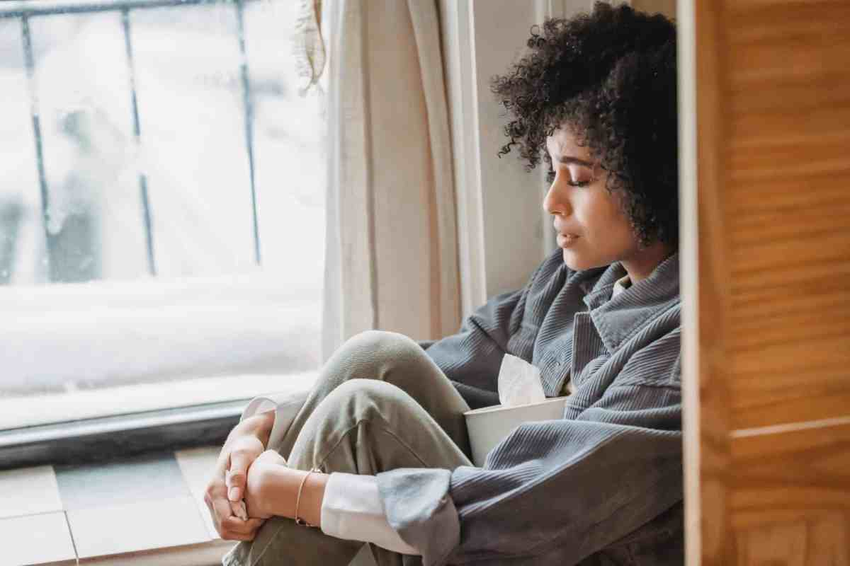 desperate black woman embracing knees suffering from difficulties
