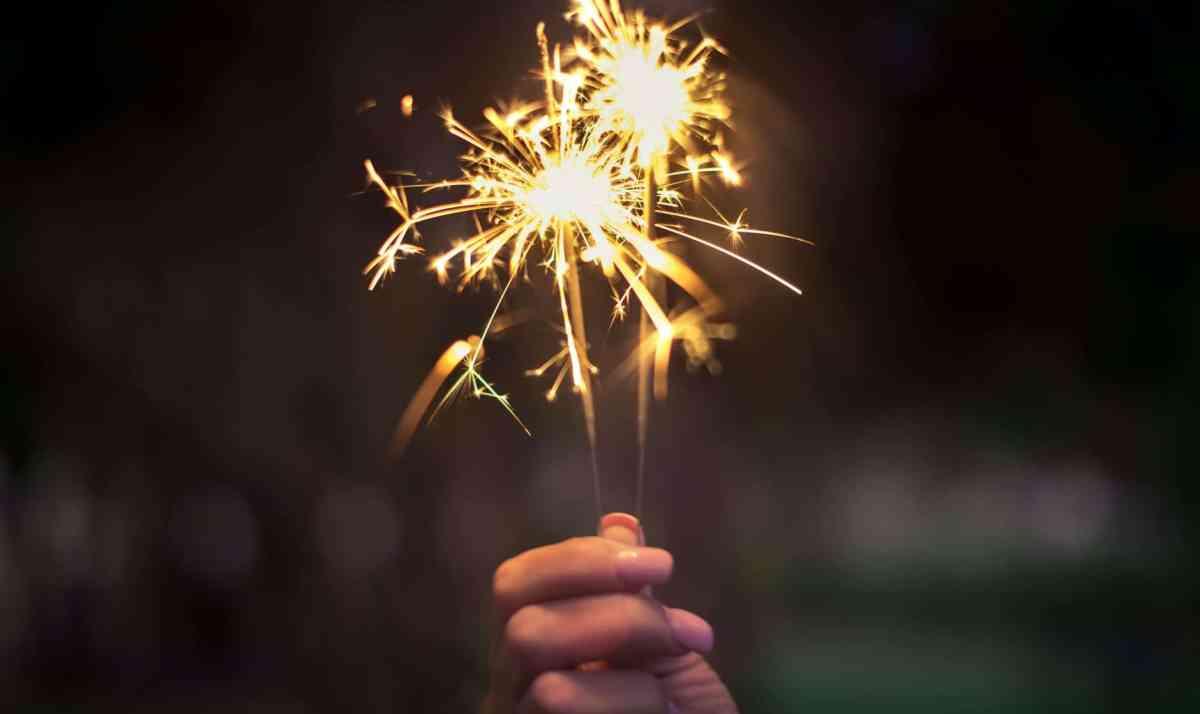 person holding lighted sparkler - make change happen