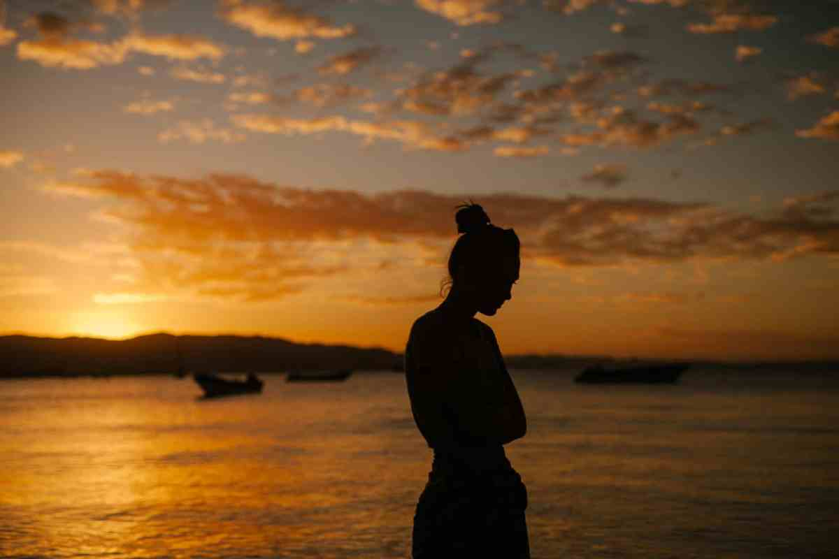 sad woman standing on coast of sea at sunset - be more present