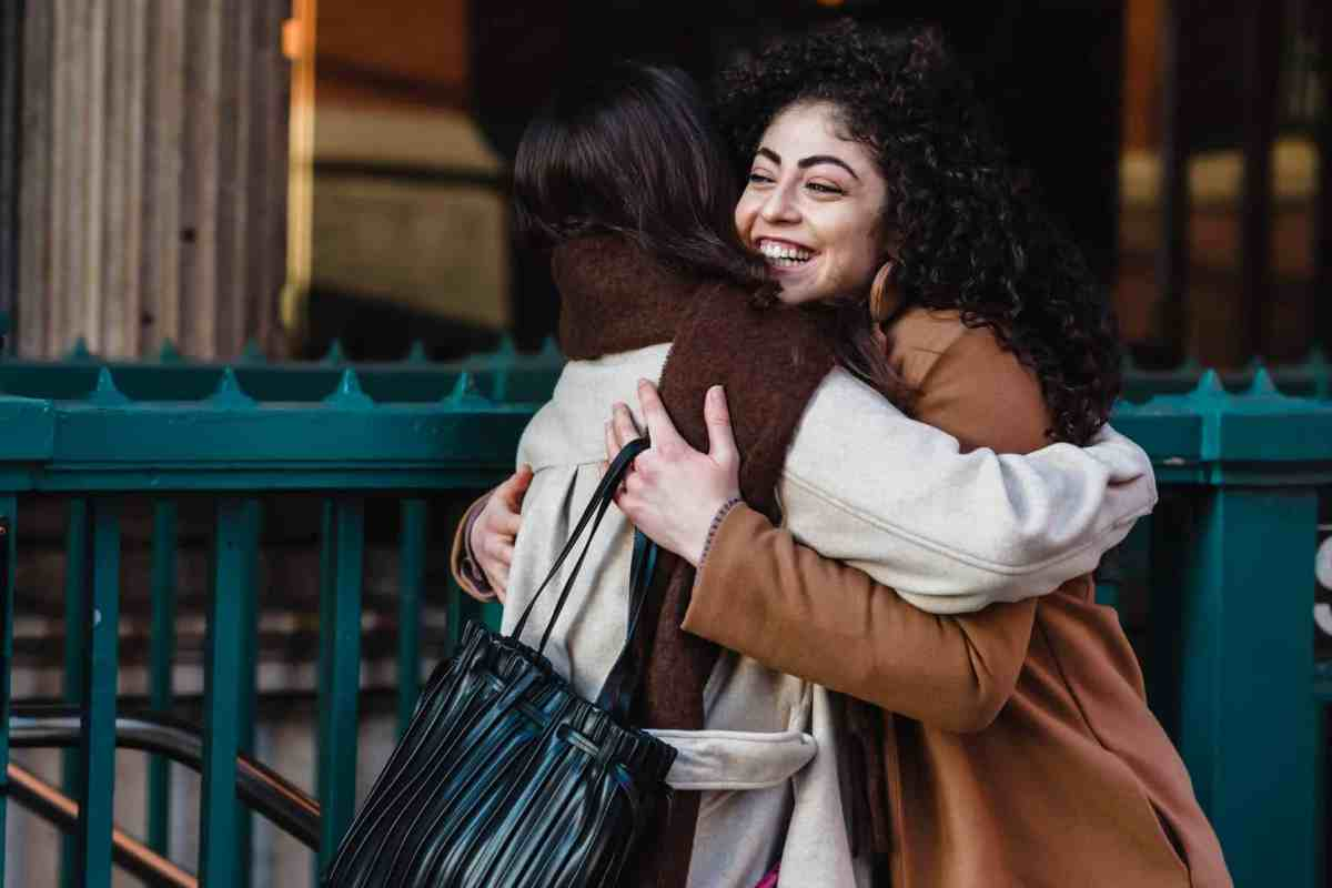 happy girlfriends hugging each other on street - common denominator theory