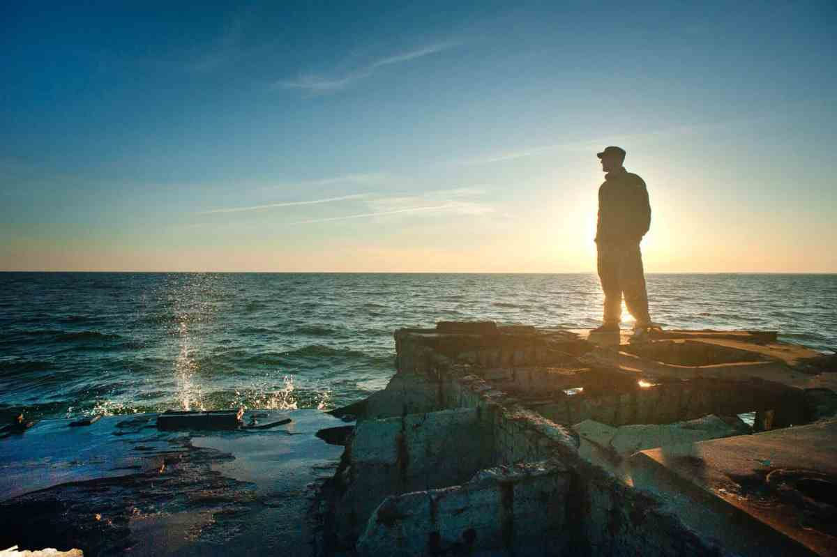 silhouette photo of man standing near the edge of concrete pavement - purpose can light you up
