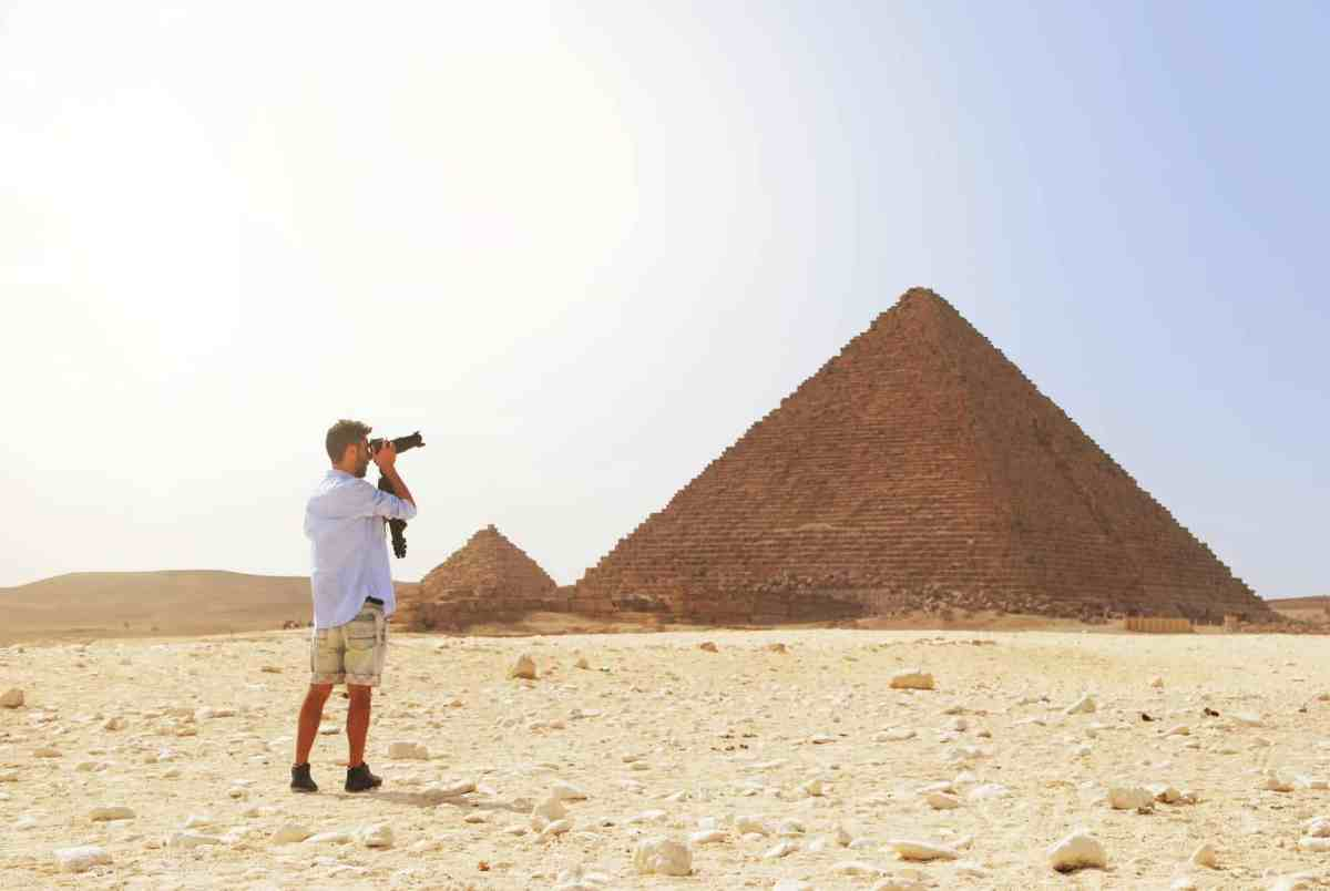 man taking photo of the great pyramid - the Abundance Pyramid
