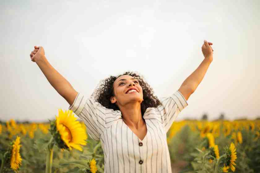 photo of woman standing on sunflower field - emotional state