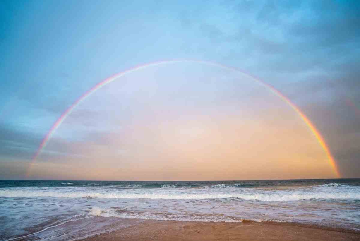 rainbow over rippling sea in nature - recognizing we're human