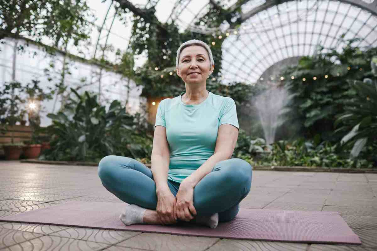 woman sitting on a yoga mat while smiling - recognizing we're human