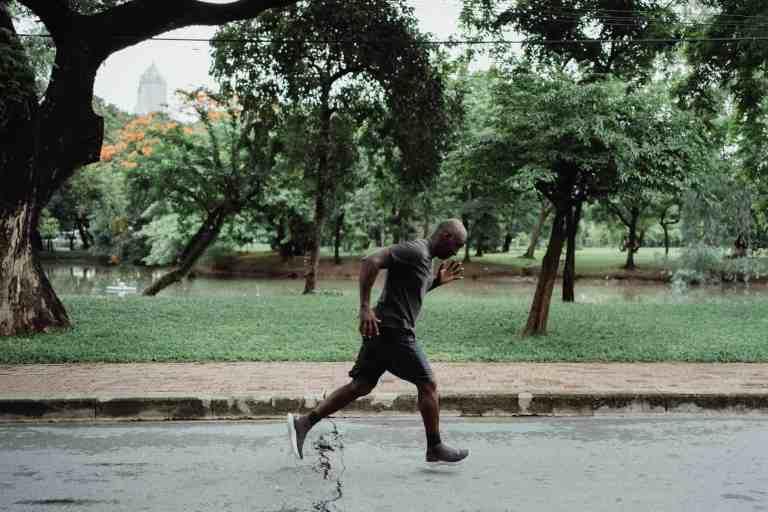 man in gray t shirt and black shorts running