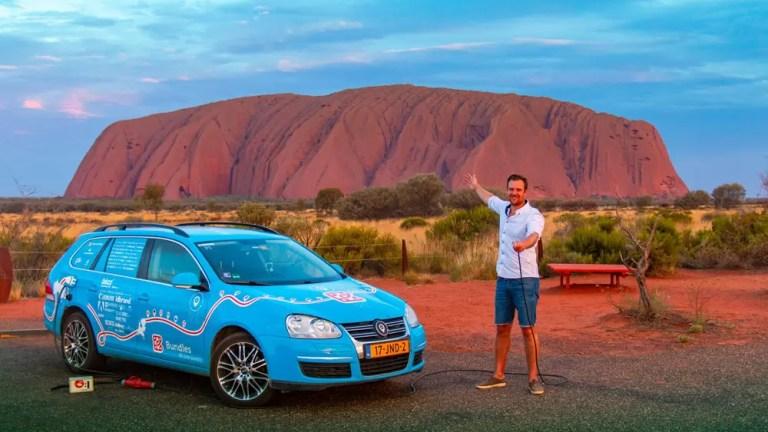 Mit Elektroauto vor dem Uluru Berg in Australien