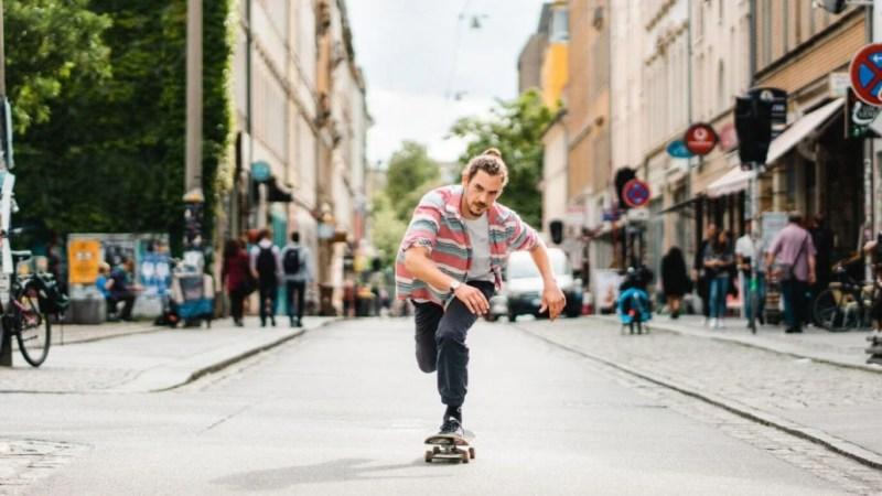 Ein Mann fährt auf einem Skateboard die eine Straße in Dresden-Neustadt.