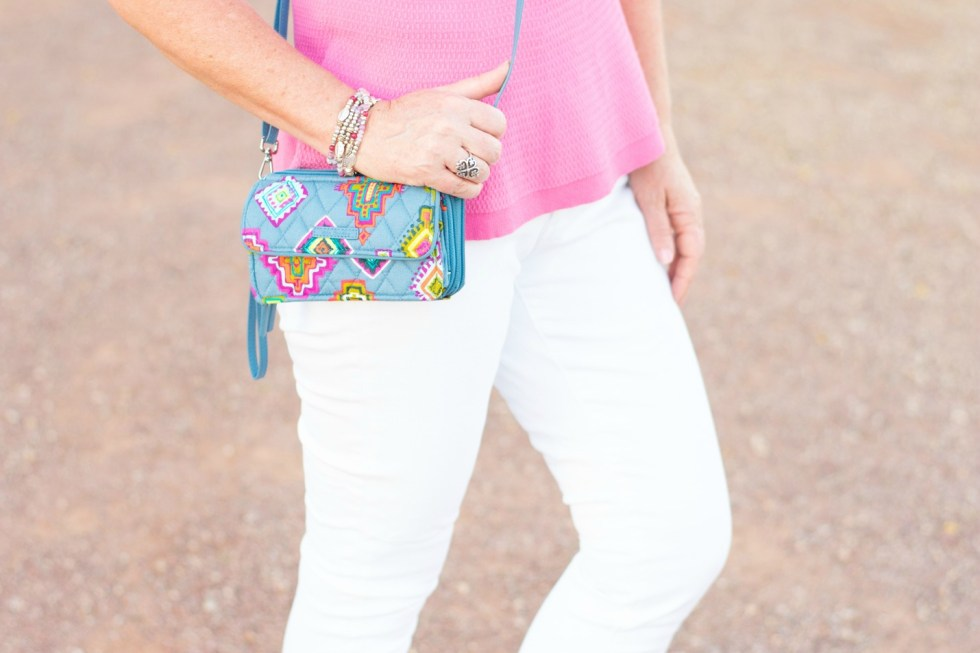 White skinny jeans accented with a Vera Bradley wristlet