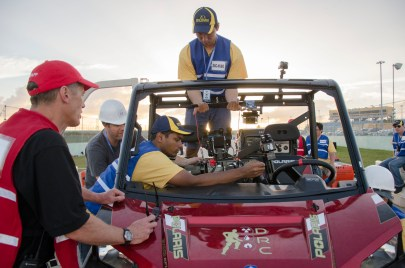 DRC-Hubo team members carefully positioned the robot in the utility vehicle as National Geographic cameras recorded the historic robotic journey.