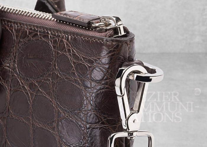men's brown bag close up nickel coated chrome joints zip table top, accessories photography on cement background styling art direction retouched colour management | Garment Merchandising Company in Hong Kong : : Styling and Imaging of Apparel Made in and Imported from Italy Reselling through e-Commerce