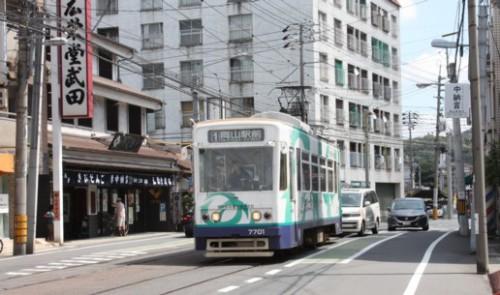 中納言電停を行く7701号(元呉市電の台車、機器を流用) うしろは吉備団子の廣栄堂