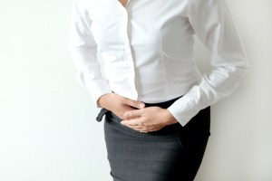 woman holding her lower abdomen out of fibroid pain