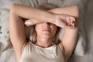 Woman laying down with her arms over her face