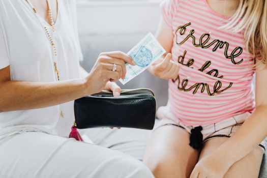 mother giving her daughter her allowance