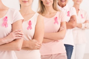 women standing together in pink with pink breast cancer ribbons