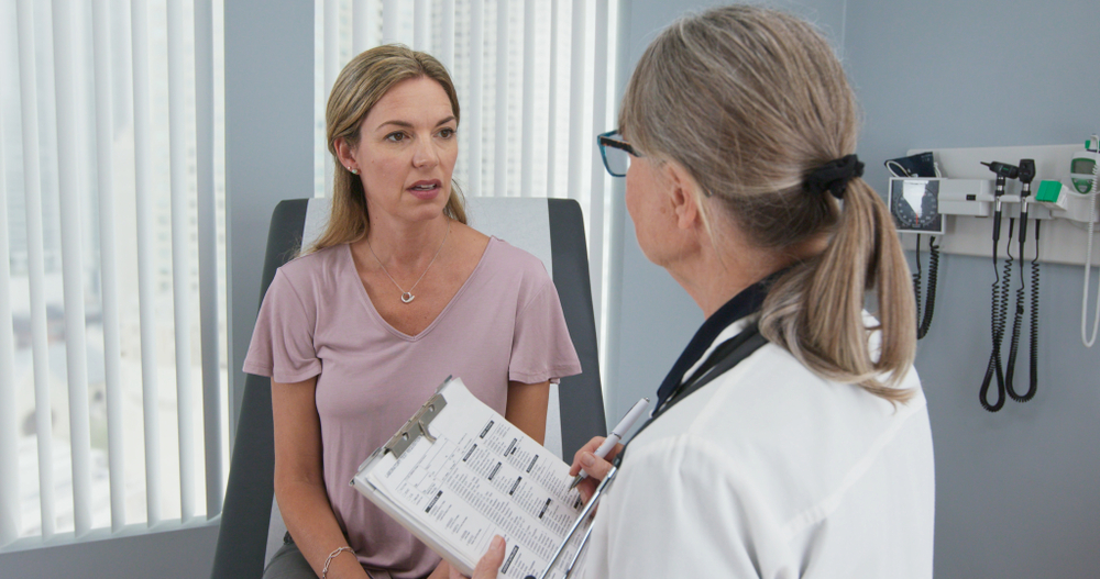 Middle-aged patient having appointment with female senior physician
