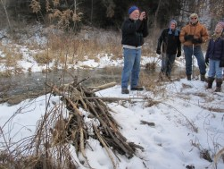 Chuck explaining beaver teeth in front of a beaver lodge. Beavers live in lodges which are different than dams and have bedrooms and eating rooms.