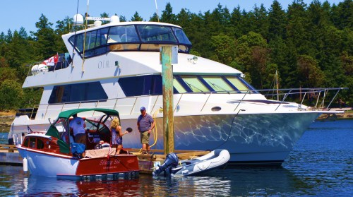 Then and now. A gorgeous 26' 1955 Chris Craft posed beside a contemporary yacht, How much is enough?