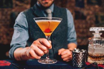 bartender serve manhattan cocktail