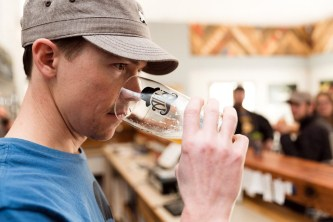 Kevin Drake, owner of Alibi Ale works, finishes his first pint of pale ale. Photo by Mike Higdon
