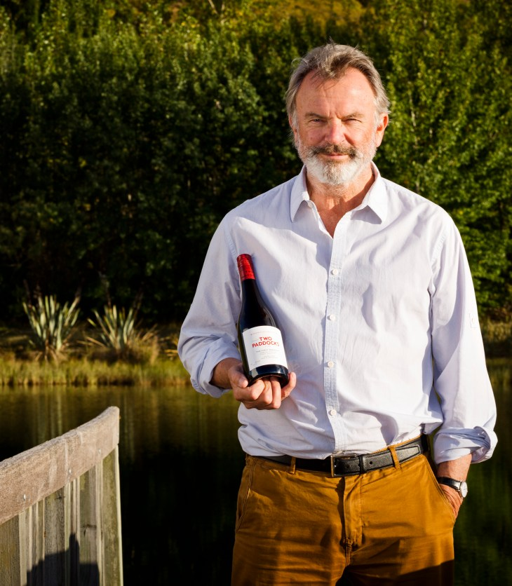 Sam Neill holding Two Paddocks Pinot Noir