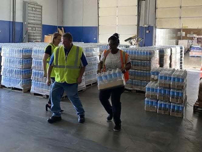 Volunteers at Buckeye, AZ terminal carrying cases of water for drivers
