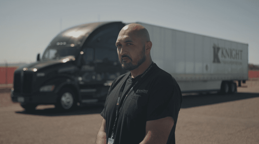 Owner Operator Truck Driver standing in front of a Knight Transportation truck