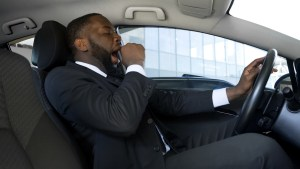 tired businessman at risk for drowsy driving crash
